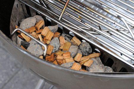 Bierblik kip van de barbecue briketten met rookhout